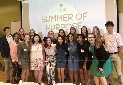 """Group of 2018 Summer Interns stands in front of """"Summer of Purpose"""" backdrop"""