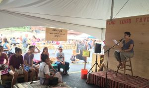 Author reads poetry onstage at Cleveland Flea
