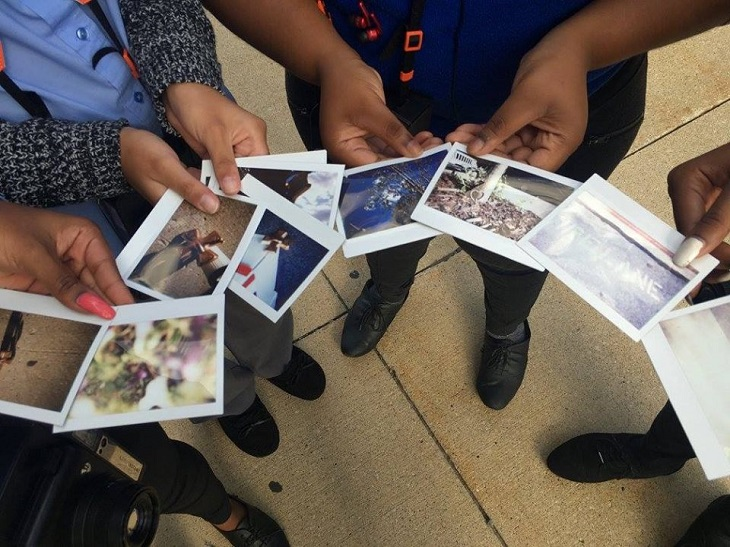 Students hold instant photographs