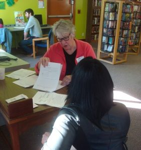 Two women sit at a library desk during a free legal clinic