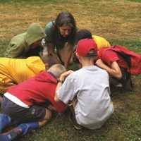 A group of children kneel around an instructor who shows them something in the grass at Shaker Lakes Nature Center