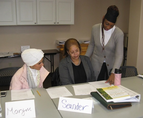 Three women sit at table for Encore volunteer training session