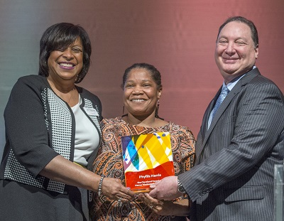 India Pierce Lee, Phyllis Harris and Ronn Richard hold the 2017 Homer C. Wadsworth Award onstage at Cleveland Foundation Annual Meeting