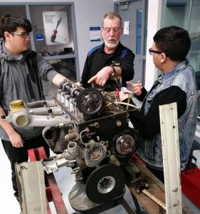 Rich Eskra, retired diesel mechanic instructs Max S. Hayes High School 12th grade diesel students on the mechanics of a snow blower.