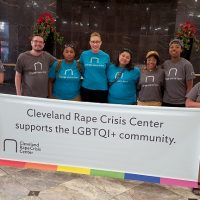 Group of students stands in front of a banner that reads Cleveland Rape Crisis Center supports the LGBTQI+ community.