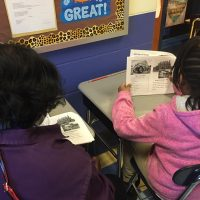 A woman sits with a young student as they read a book together