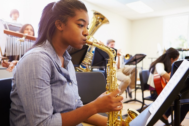 Female Pupil Playing Saxophone In High School Orchestra