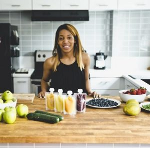BabyMunch founder LeAnna Miller poses with fresh fruits and vegetables and her baby food product