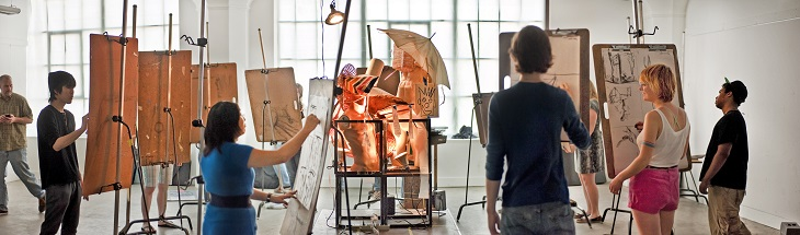 Art students stand at easels in a studio