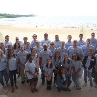 Large group of people pose for a picture on Edgewater Beach wearing Cleveland Leadership Center shirts