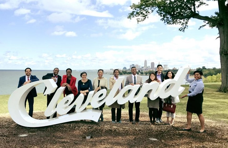 Cleveland Foundation fellows stand in front of Cleveland script sign with Lake Erie and Cleveland skyline behind