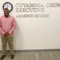 Ricardo stands in front of the Cuyahoga County seal on the wall of the county offices