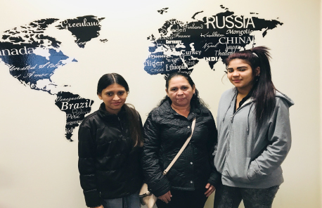 Three immigrant women - Kittys, Anita and Nayeli - stand in front of world map
