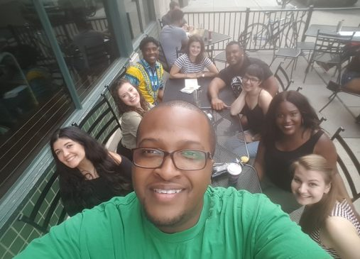 Eli takes a selfie the 9 other members of his fellowship cohort