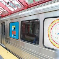 An image of the side of an RTA train at the station platform with windows decorated in colorful art