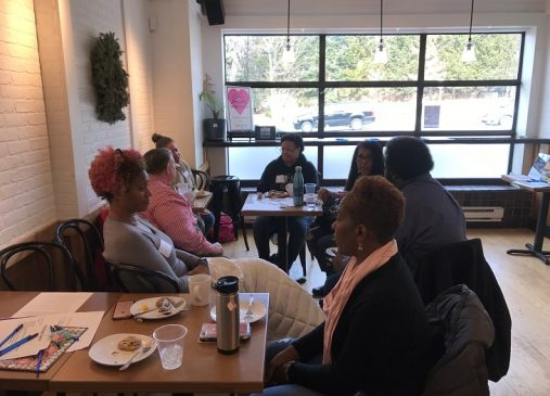 a group of women sit around a table in discussion