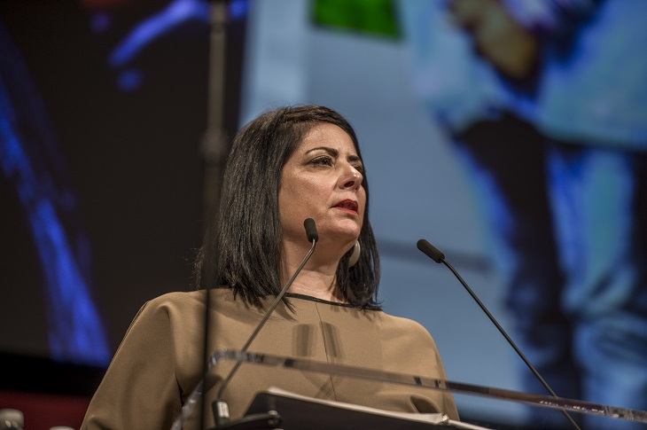Lillian Kuri speaks from podium onstage at annual meeting