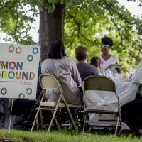 A common ground yard sign is visible in front of a group of people seated at a table outdoors