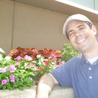 Frank Jason Feola stands smiling in front of flower bed