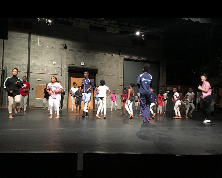 A group of students practice a dance routine on stage