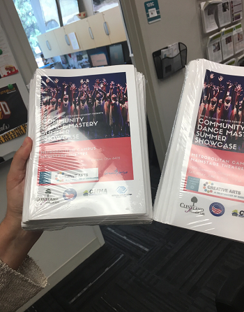 Noni holding printed programs for TriC summer camp