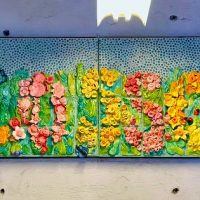 Mixed media work of art spells out the word blossom in flowers