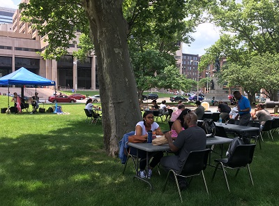 Image of people sitting outside eating lunch at memorial mondays