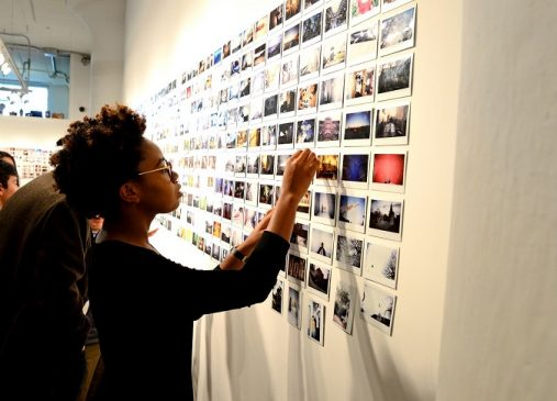 A young girl points to a wall of pictures taken by Cleveland Print Room students