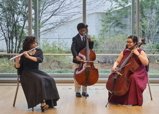 Three students play classical instruments on stage