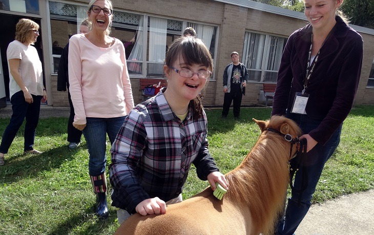 A young girl with Down Syndrom pets a miniature horse