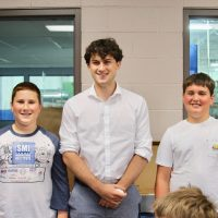 Nathan stands next to two younger boys