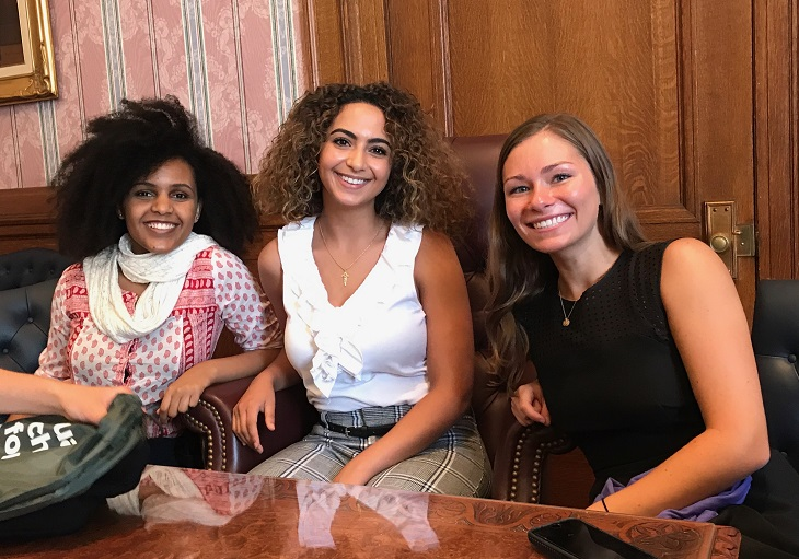 Christina sits with two fellow summer internship cohort members
