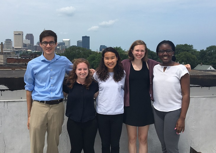 Group of summer interns stands in front of Cleveland skyline