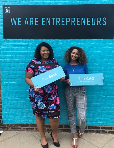 """Christina and colleague stand in front of blue wall that reads """"We are Entrepreneurs"""""""