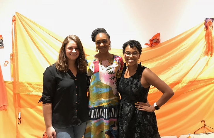 Three women stand in front of orange backdrop