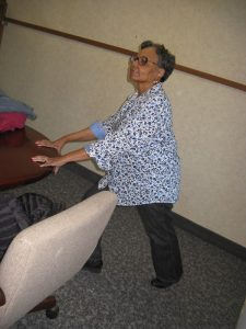 A woman stretches at a table