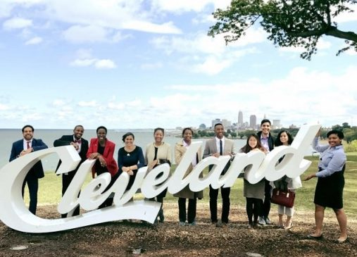 Public Service Fellows stand behind Cleveland script sign with skyline in background