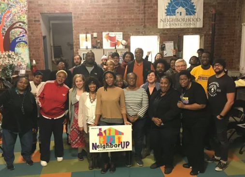 A group of grant recipients and neighbor up network members pose with Neighbor Up yard sign